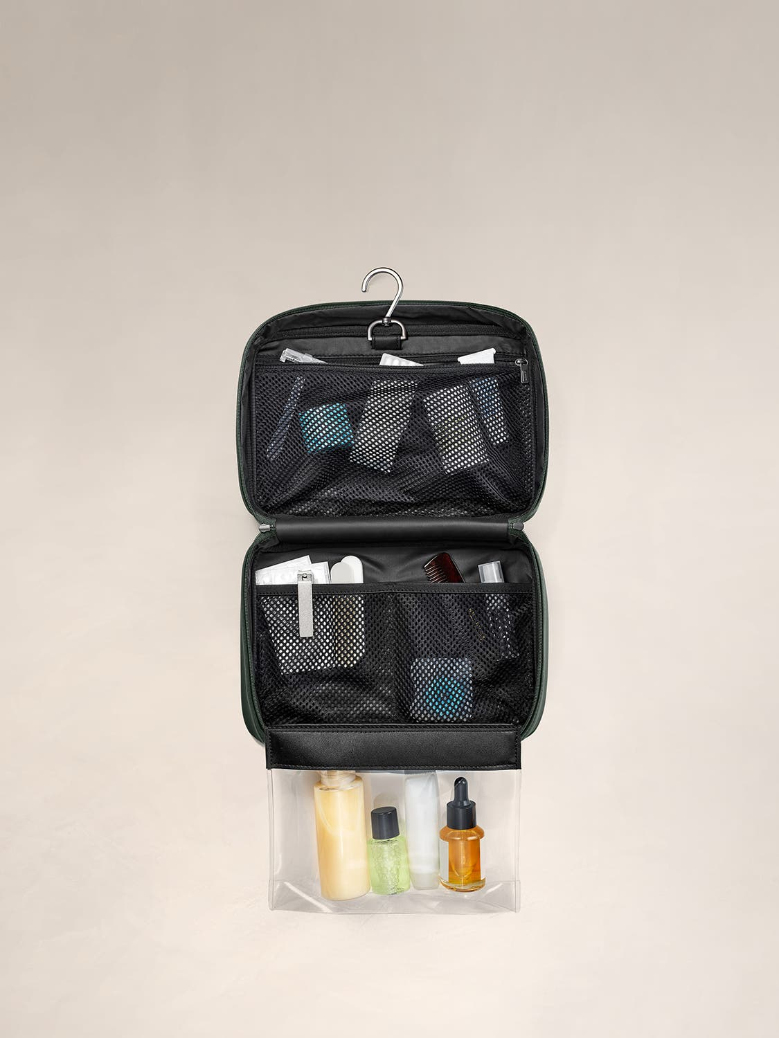 An internal view of a green toiletry bag packed with travel accessories within mesh pockets.