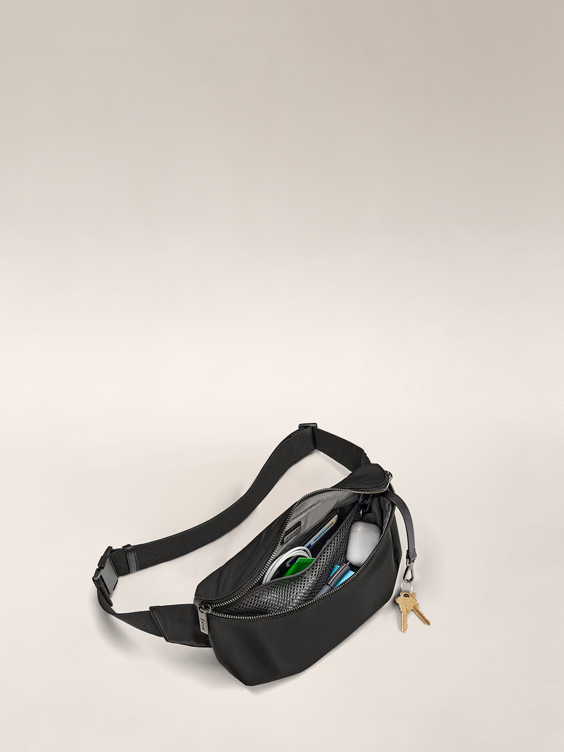 Open view of a black fanny pack with wire cable, pen and more organized in internal pockets.