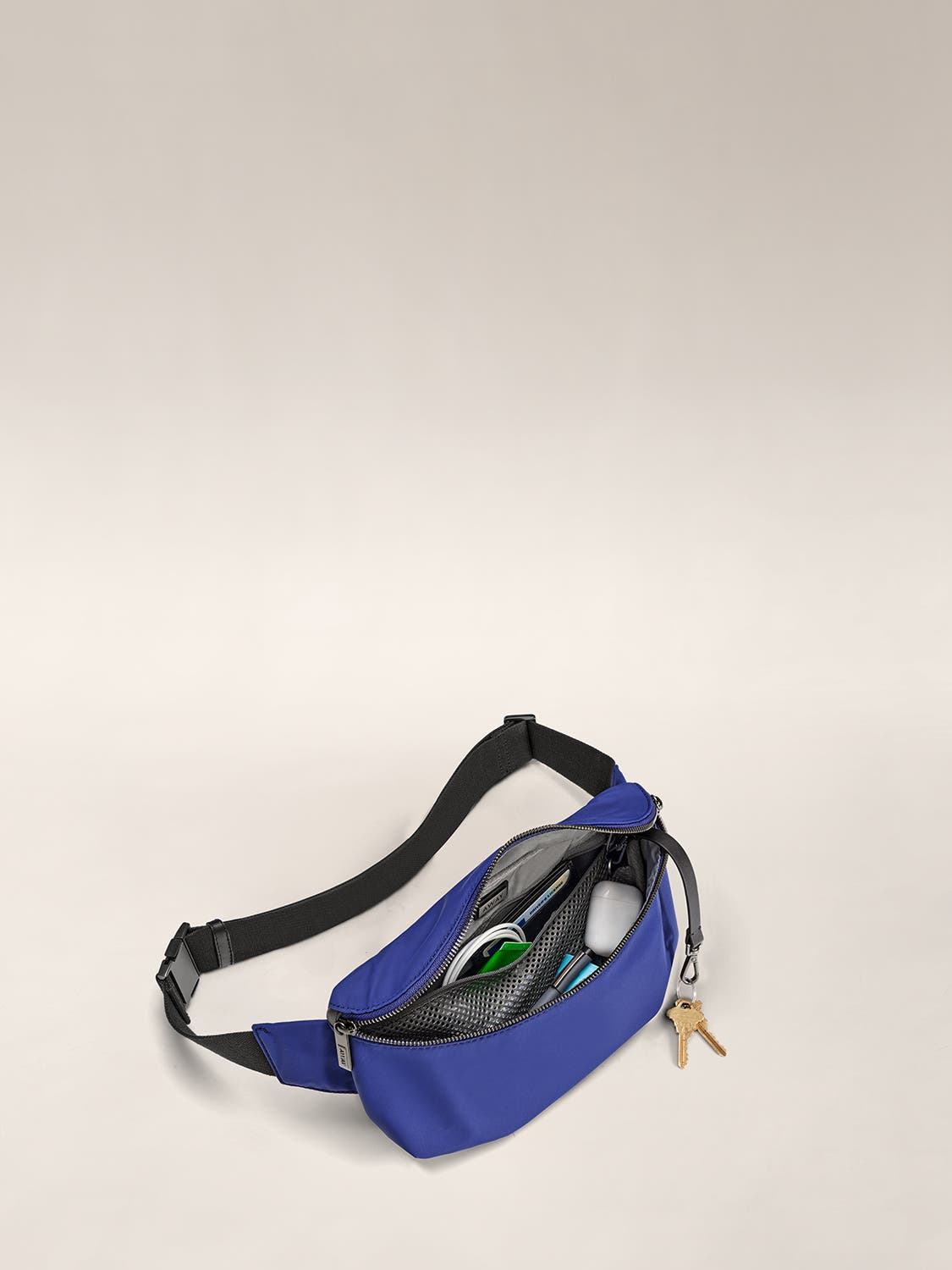 Open view of a cobalt fanny pack with wire cable, pen and more organized in internal pockets.