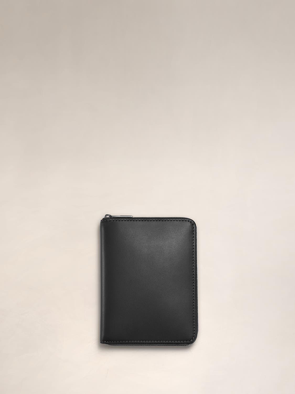 A black wraparound zip wallet for travel.