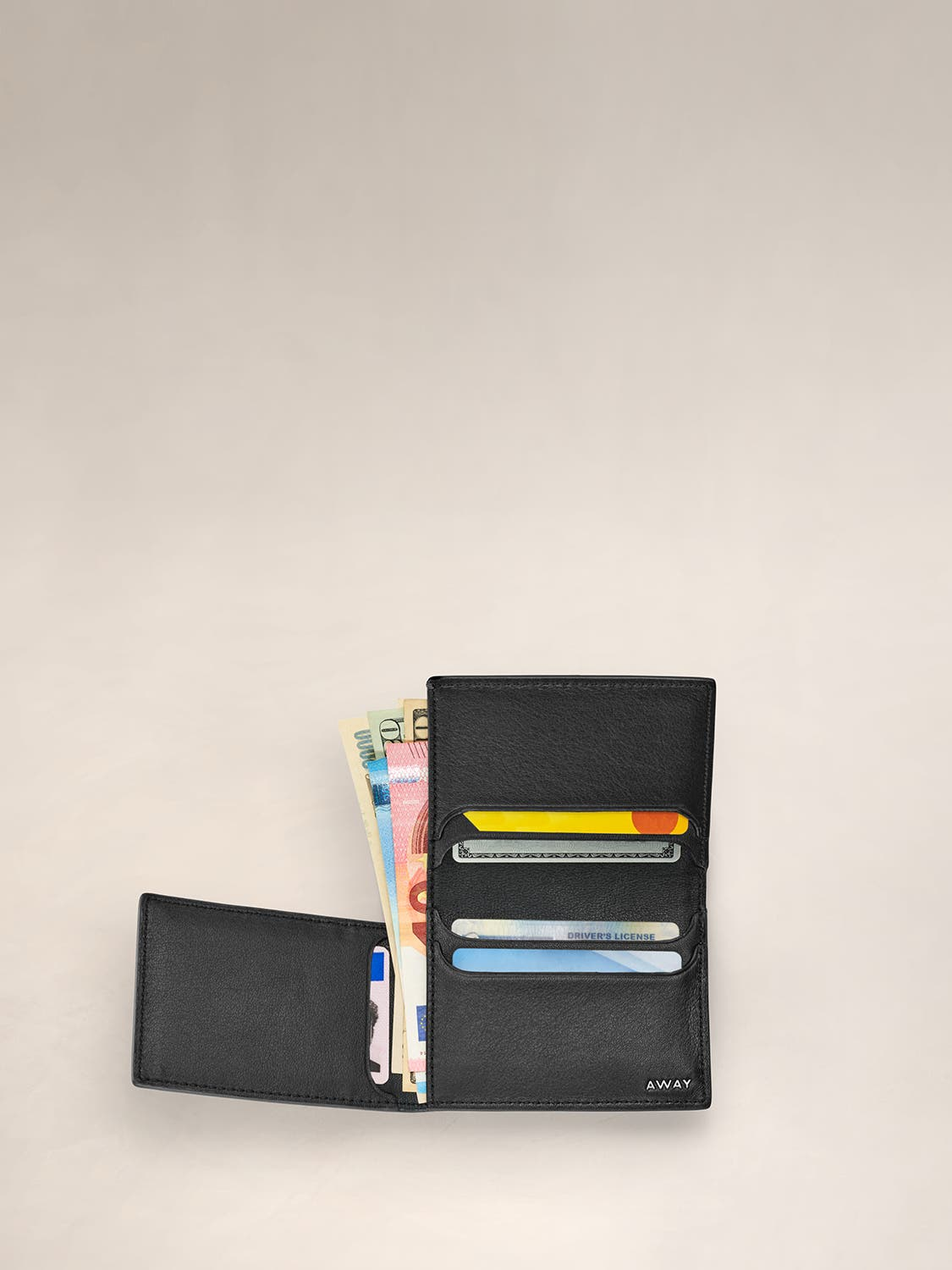 An open view of a black L Fold wallet with cards and cash inserted in various pockets.