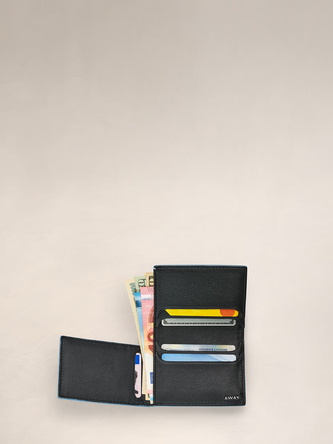 An open view of a coast L Fold wallet with cards and cash inserted in various pockets.