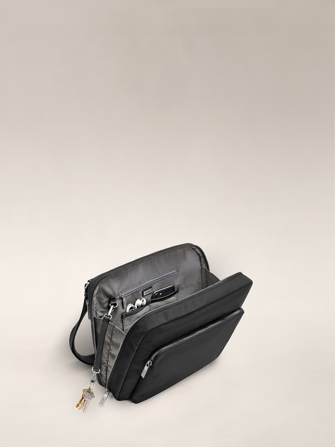 Open inside view of a black messenger bag with grey lining with technical accessories organized in small pockets.