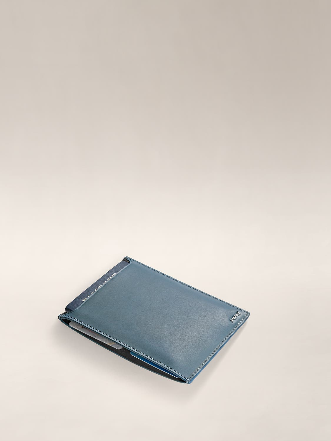 Horizontal view of a slim passport holder with documents inside.