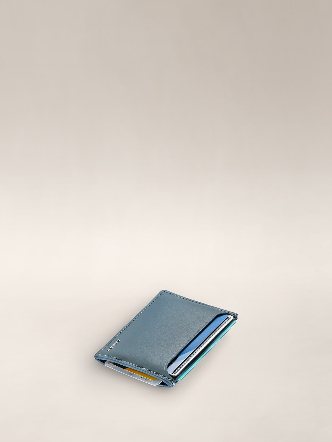 Horizontal view of a slim card holder with cards inserted in various top and side panel pockets.