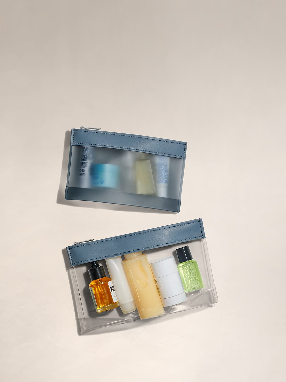 A TSA approved clear pouch set for travel full of toiletries.