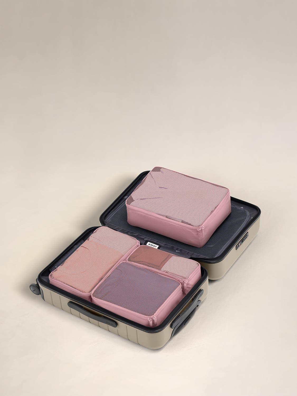 Blush travel packing cubes displayed in an Away suitcase