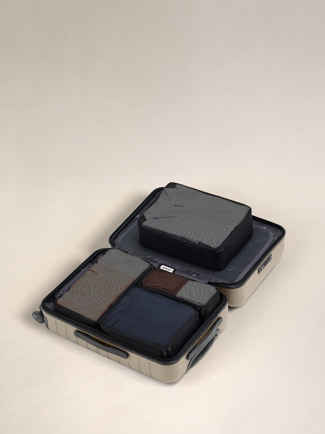 Black travel packing cubes displayed in an Away suitcase