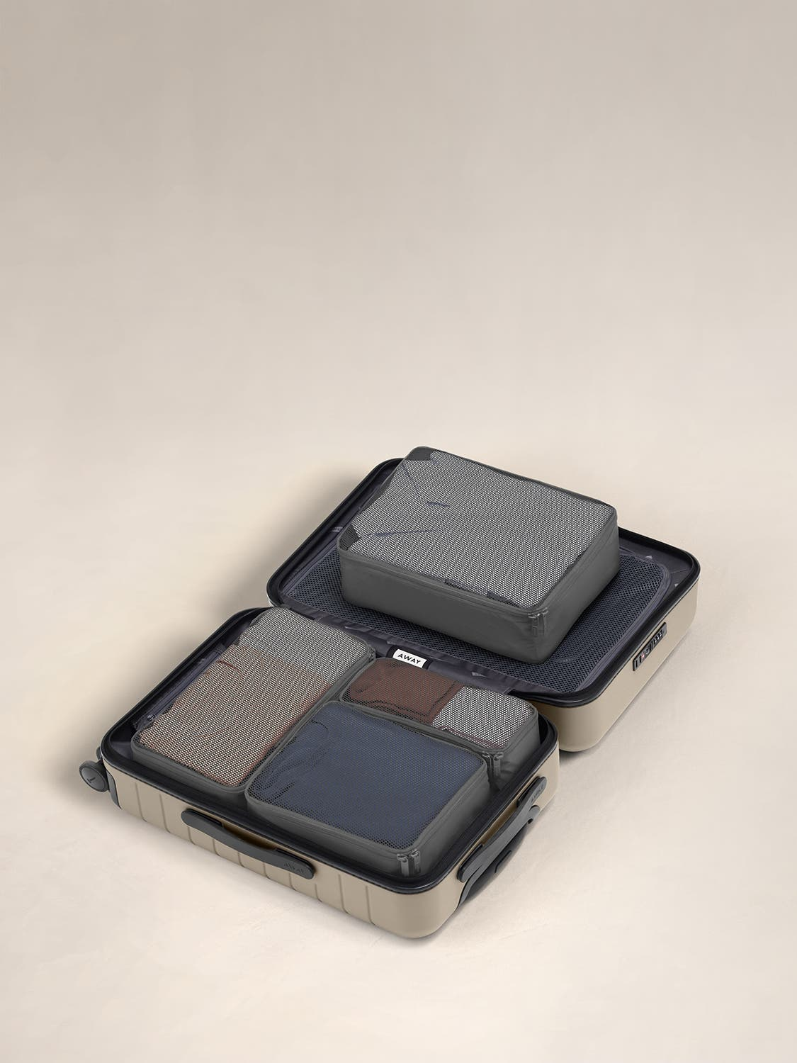 Asphalt travel packing cubes displayed in an Away suitcase