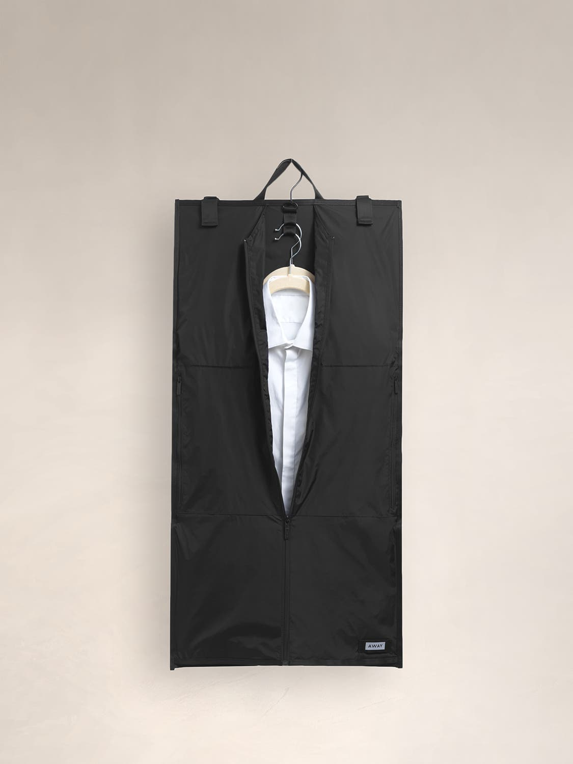 A black garment sleeve with a handle for hanging and a white shirt inside.