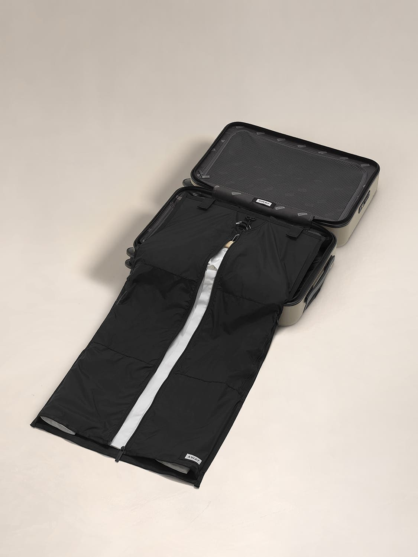 A garment sleeve open inside a open suitcase.