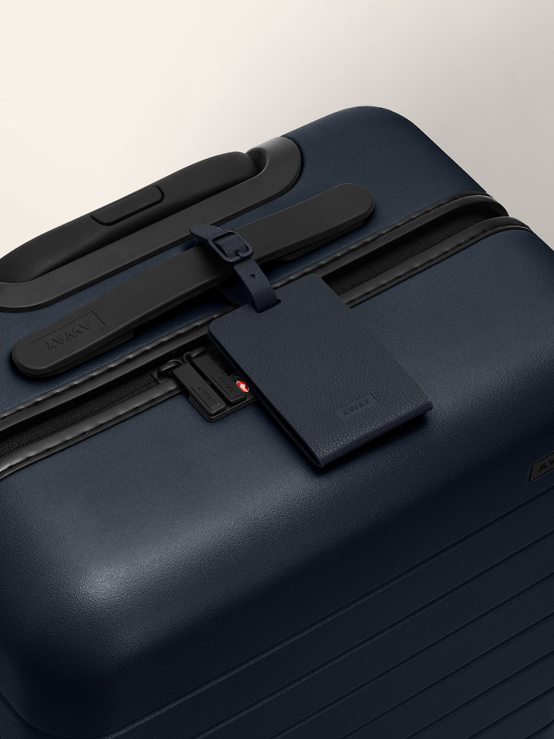 A navy color luggage tag strapped to a black handle on a navy suitcase.