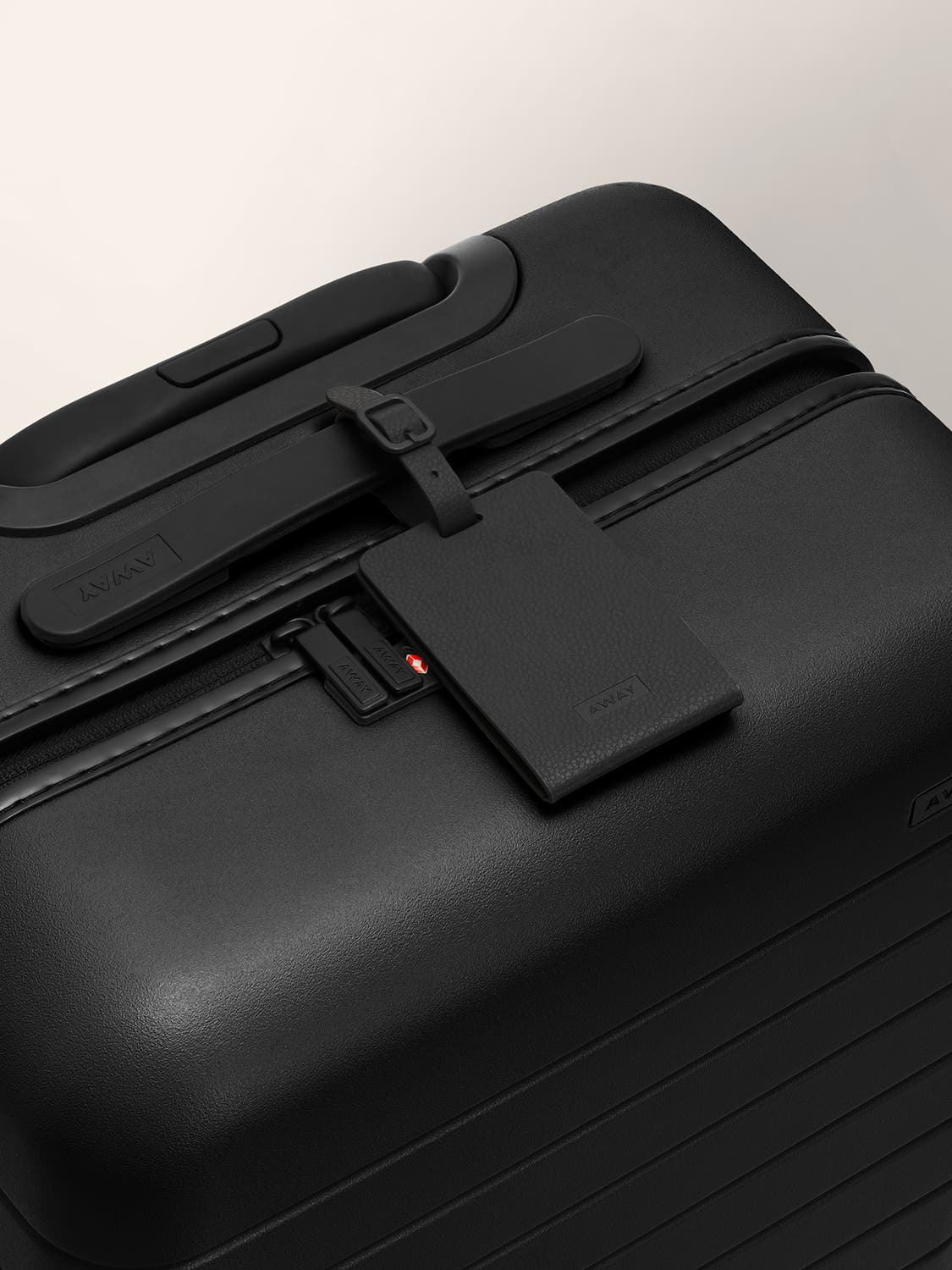A black color luggage tag strapped to a black handle on a black suitcase.