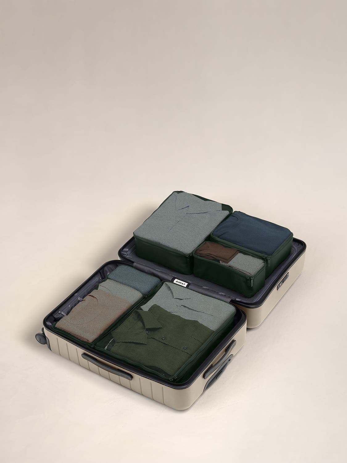 Green travel packing cubes displayed in an Away suitcase