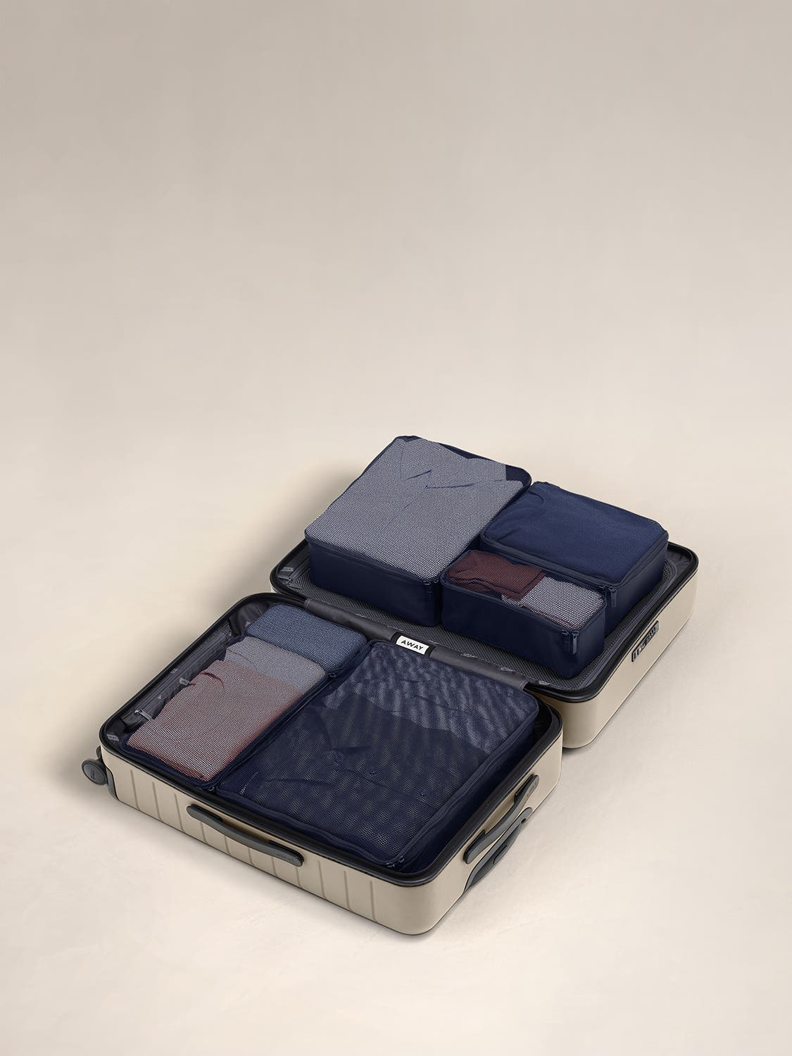 Navy travel packing cubes displayed in an Away suitcase