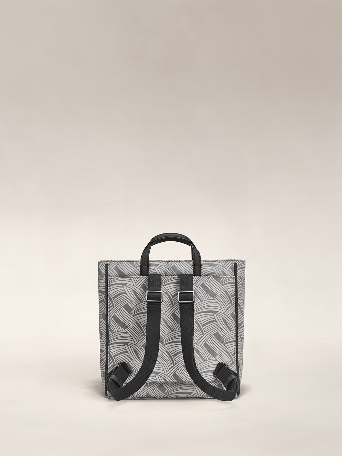 The back of a patterned grey tote with backpack straps in black.