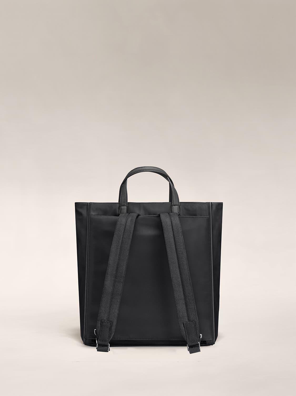 Back of a black shoulder bag with backpack straps.