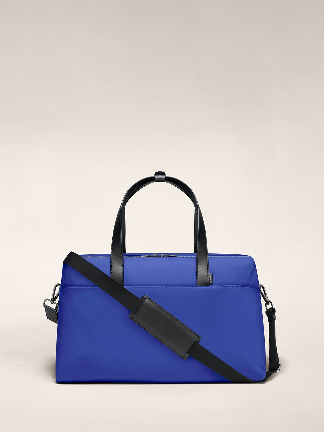 Large duffle bag in cobalt with raised handles and shoulder strap across the bag.