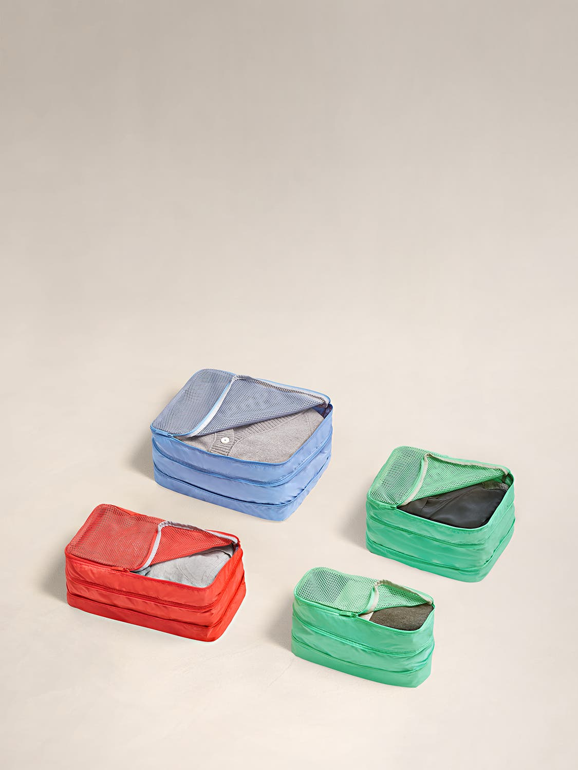 Set of four multicolor expandable packing cubes in with clothes in it
