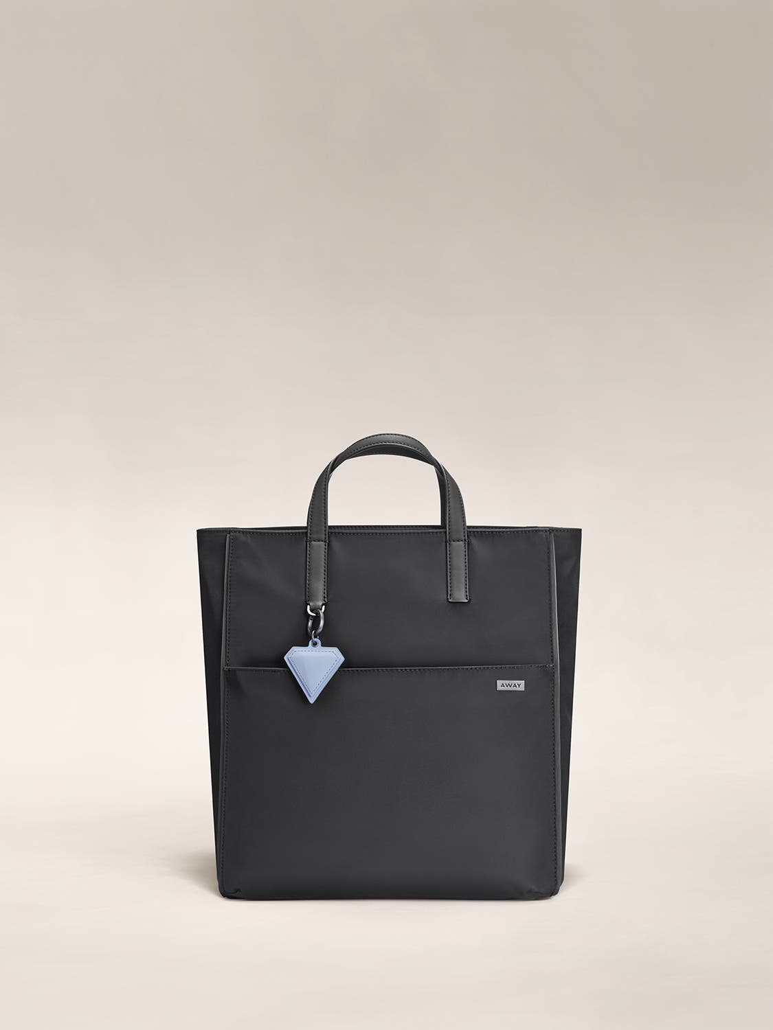 A black shoulder bag with a front zip pocket, raised leather handles and a blue charm hanging on one end.