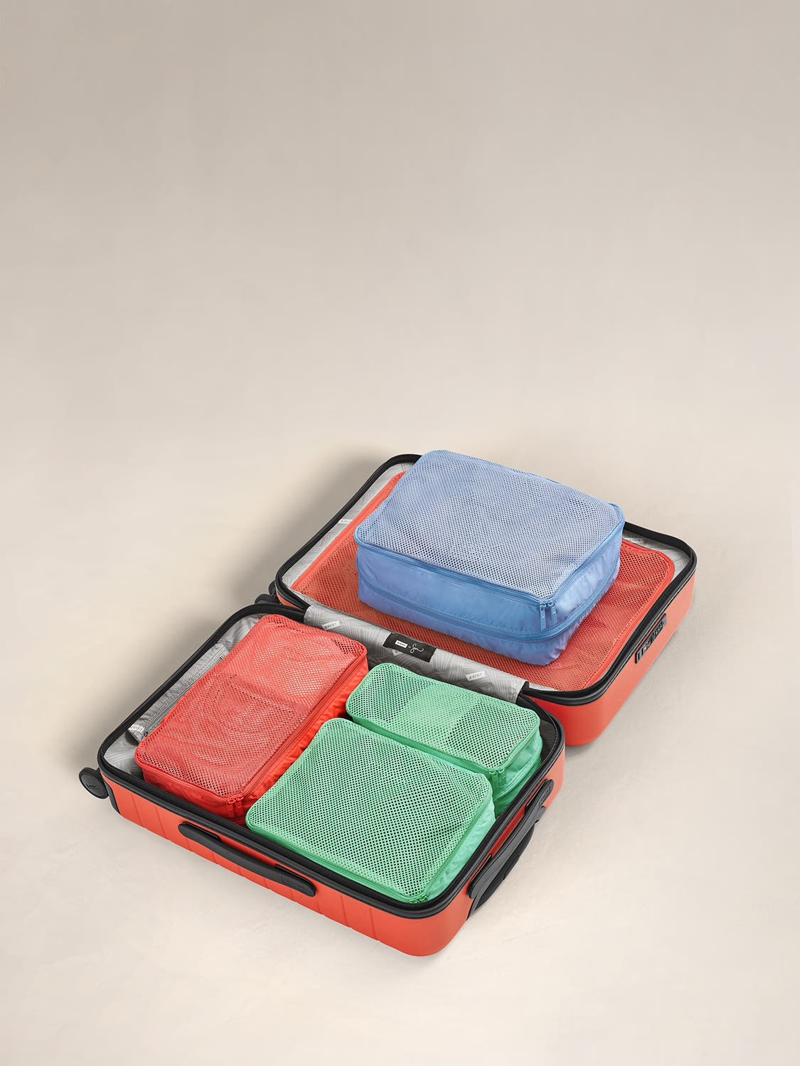 Multicolor expandable travel packing cubes displayed in an Away suitcase