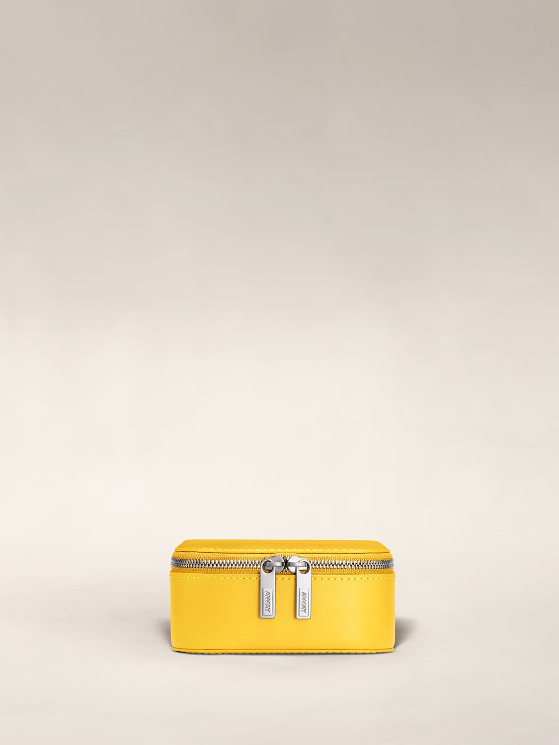 Front view of a golden yellow jewelry box zipped with Away logo on zip.
