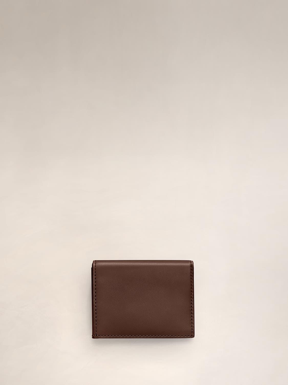 A chestnut L-Fold wallet for travel.