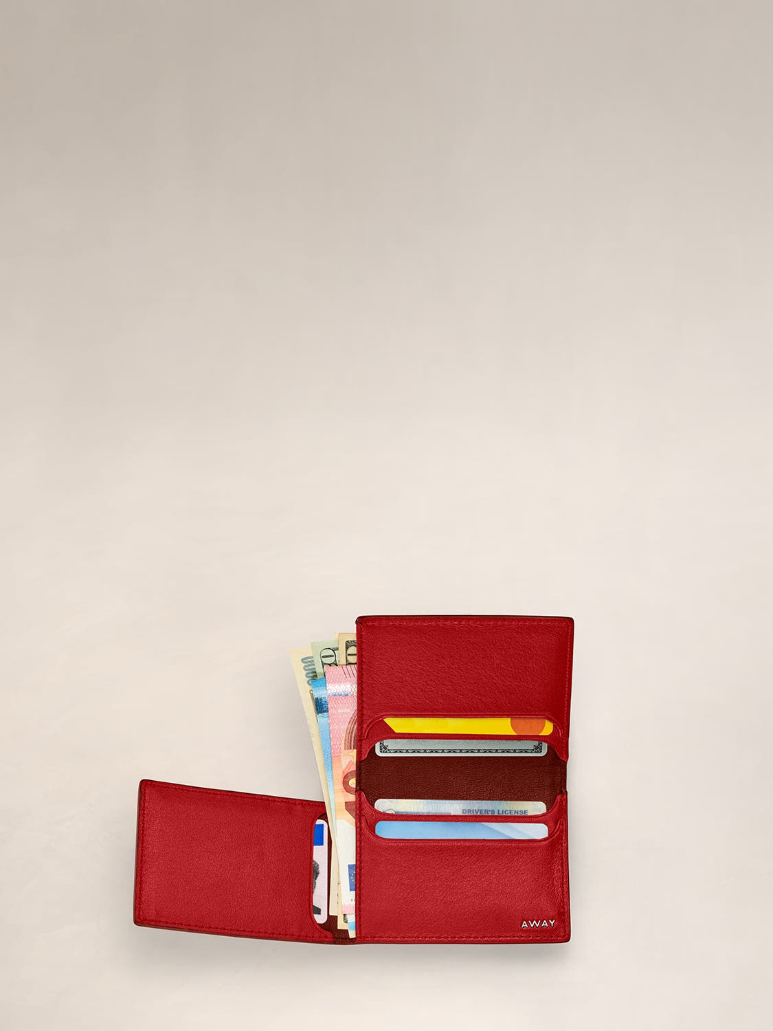 An open view of a chestnut L Fold wallet with cards and cash inserted in various pockets.