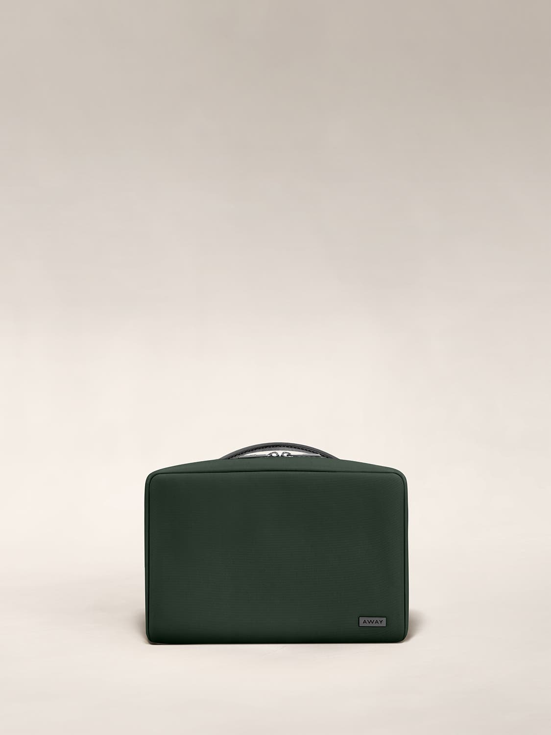 Small travel toiletry bag in the color green by Away.