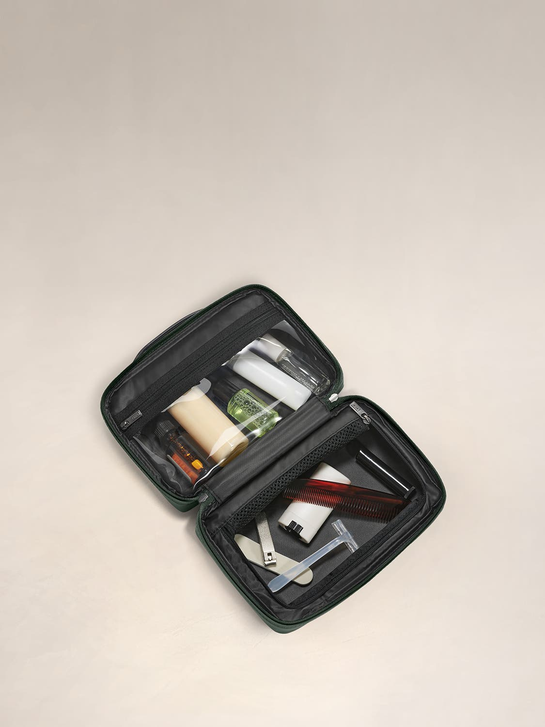 Inside view of a small toiletry kit in green with interior pockets shown and full of travel toiletries.