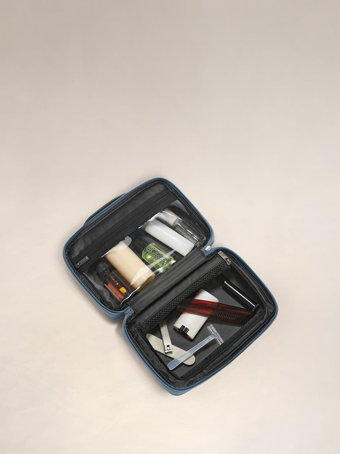 Inside view of a small toiletry kit in coast with interior pockets shown and full of travel toiletries.