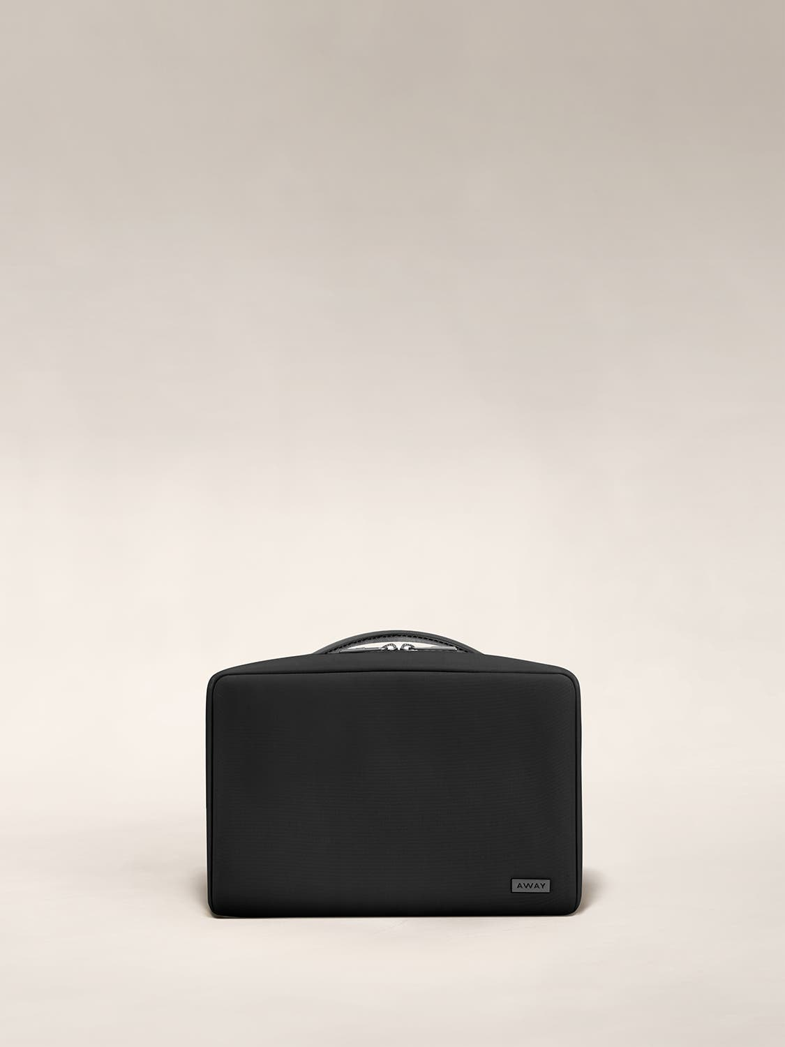Small travel toiletry bag in the color black by Away.