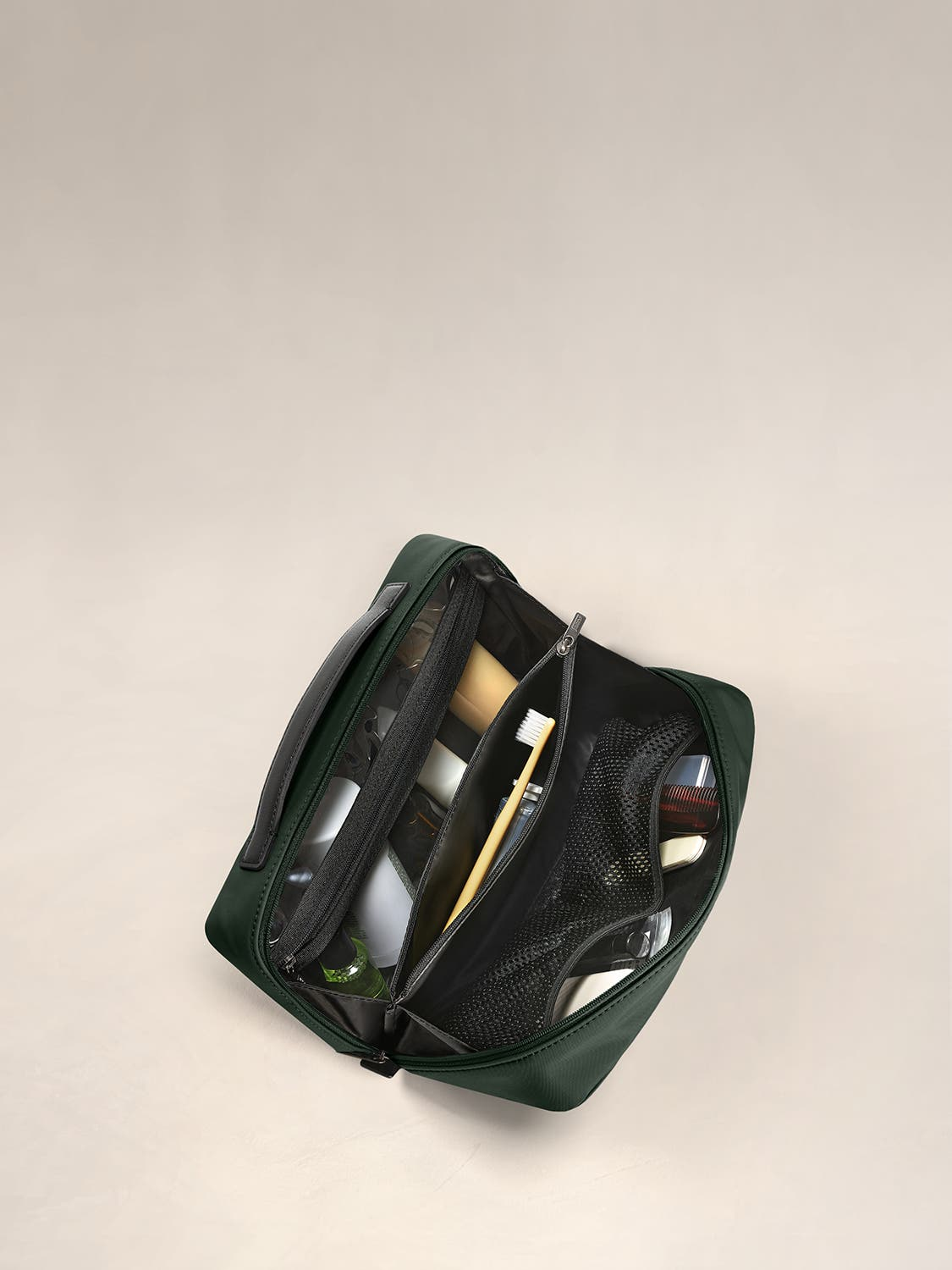 Inside view of a travel toiletry kit in green with black interior pockets full of travel toiletries.