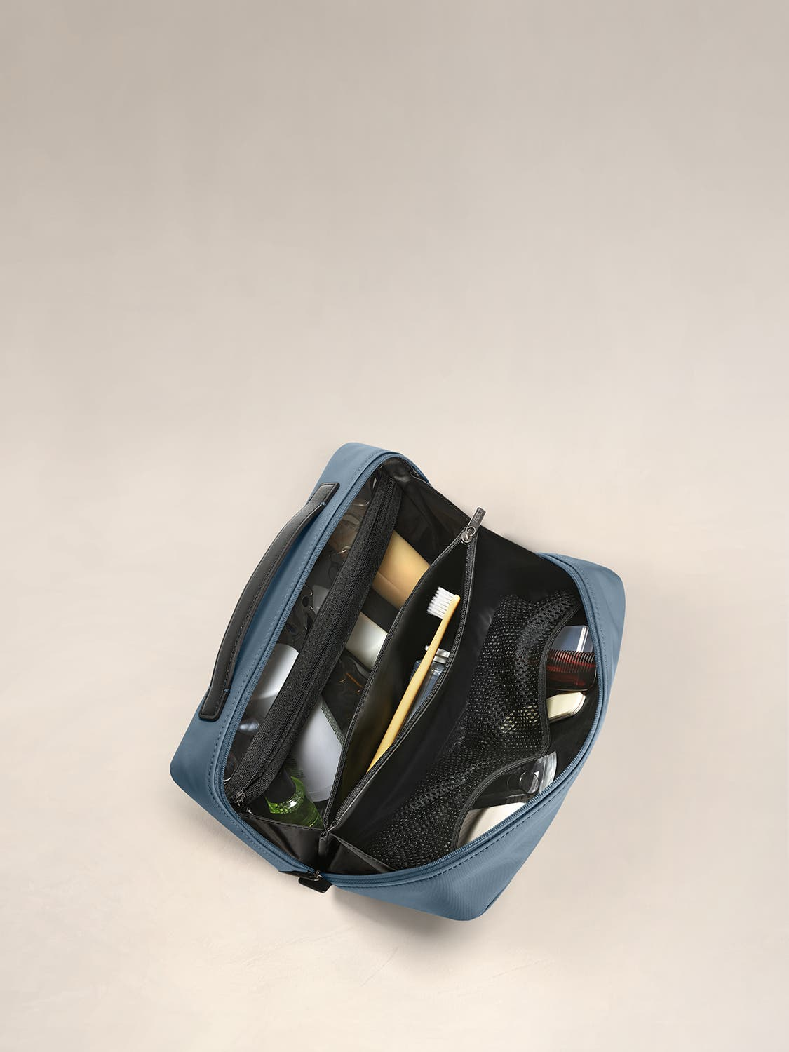 Inside view of a travel toiletry kit in coast with black interior pockets full of travel toiletries.