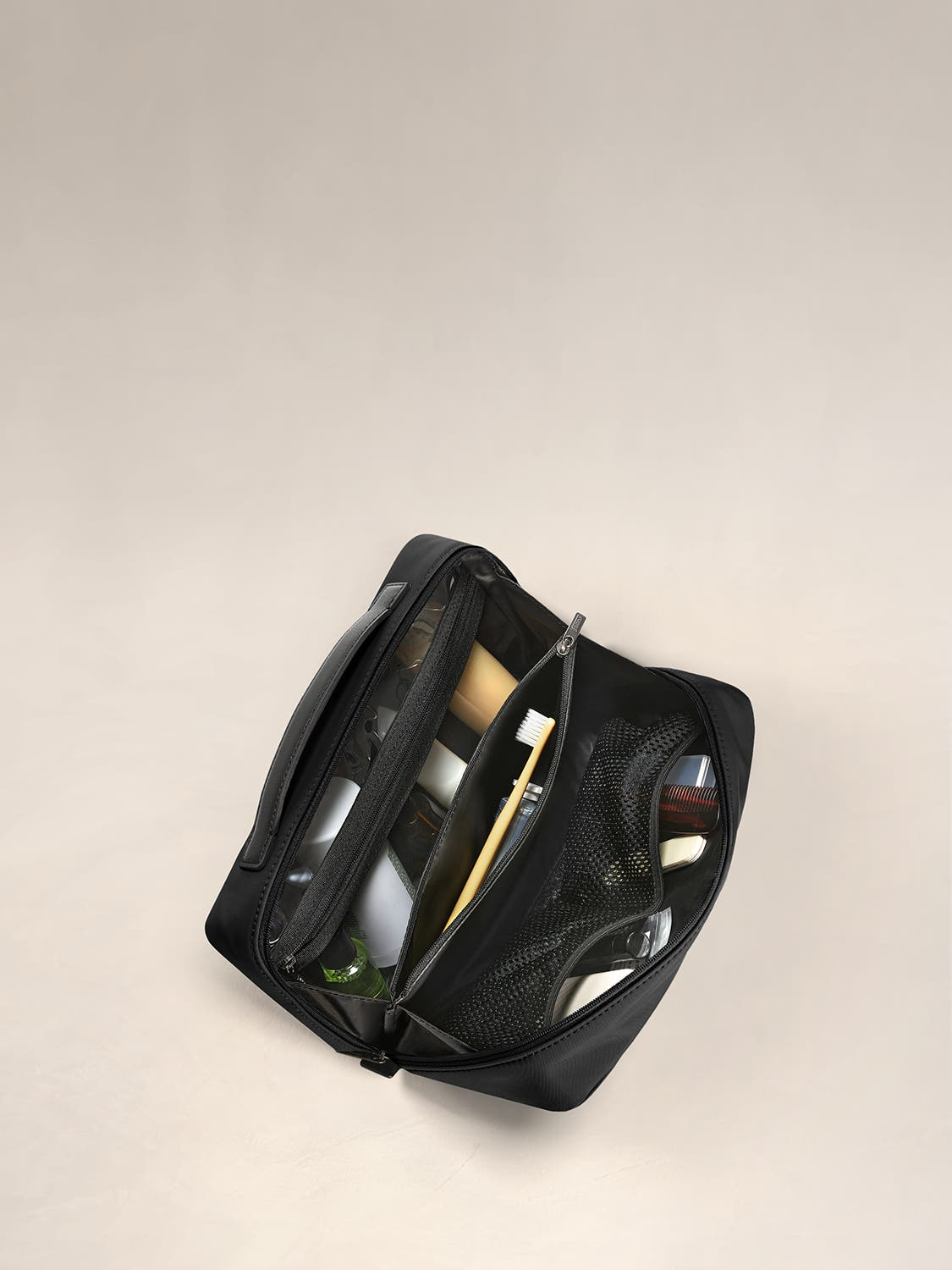 Inside view of a travel toiletry kit in black with black interior pockets full of travel toiletries.