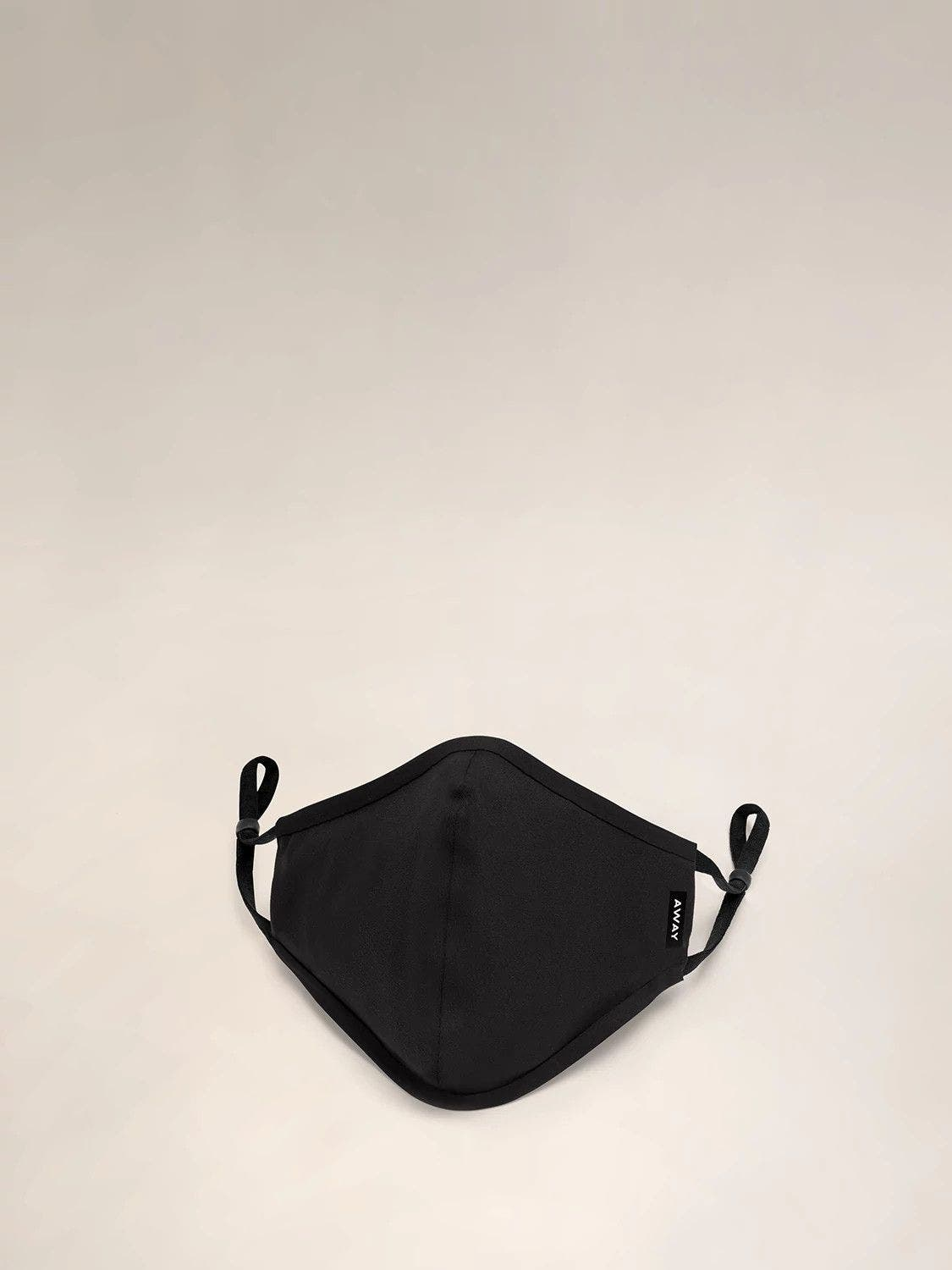A front view of a black reusable cloth face mask with ear loops shown.