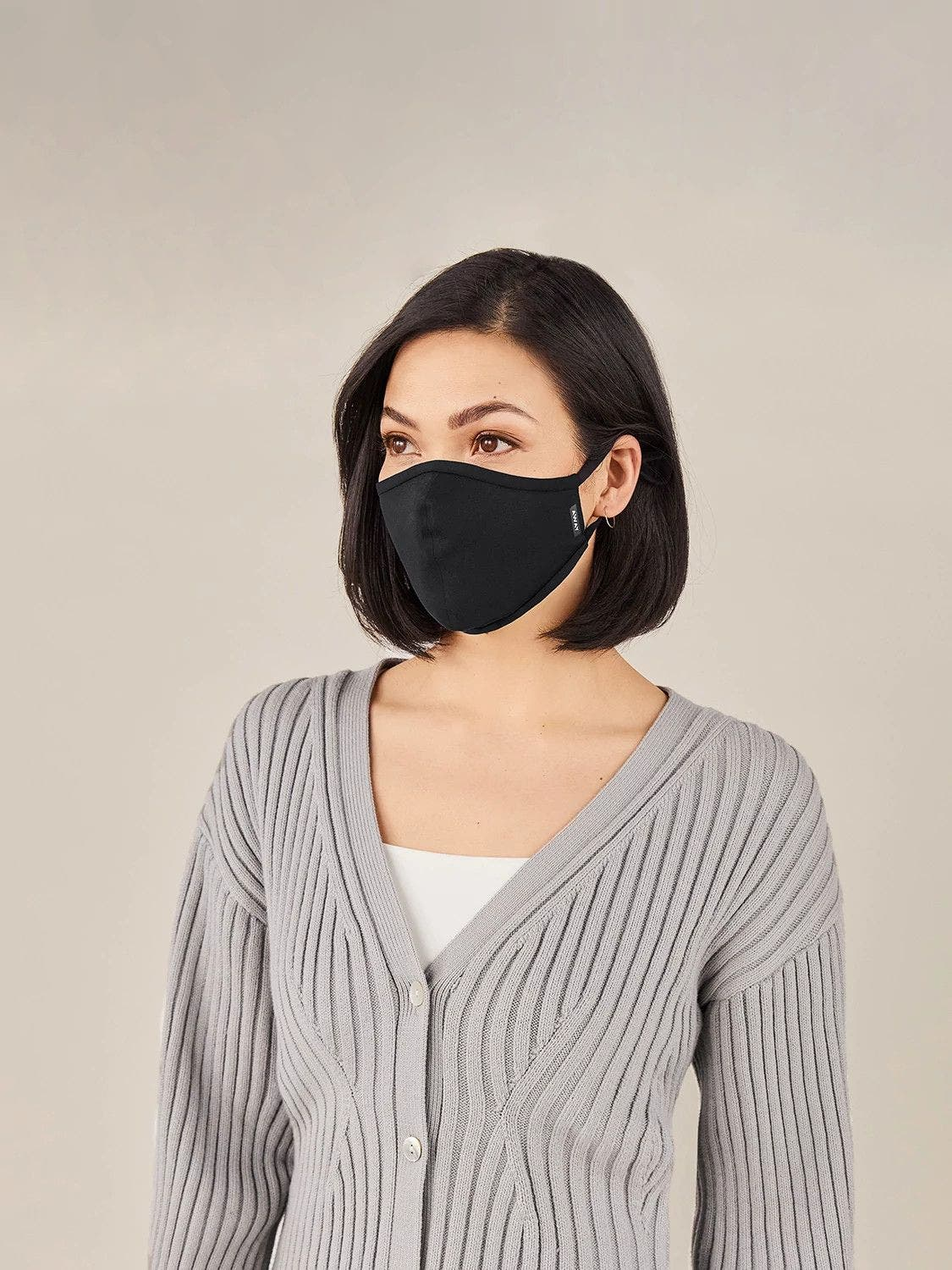 A woman in a grey sweater wearing a black reusable cloth face mask.