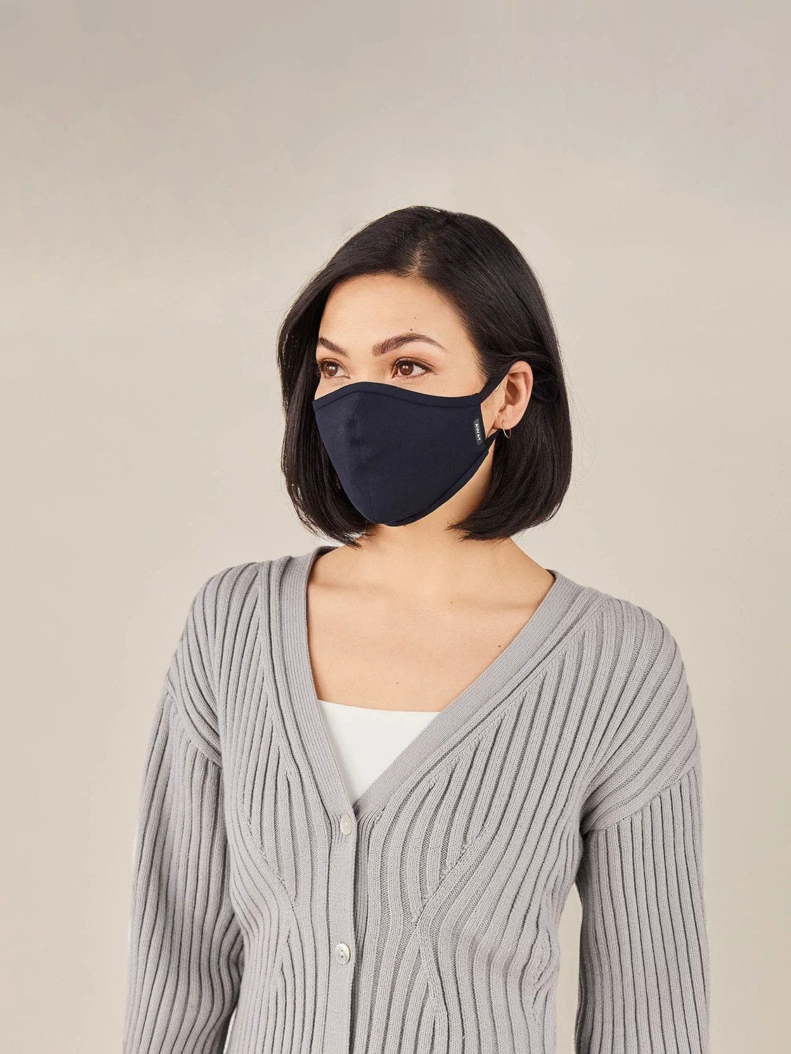 A woman in a grey sweater wearing a navy reusable cloth face mask.