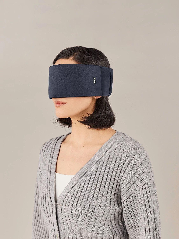 A woman wearing a navy Away travel sleep mask across her eyes.