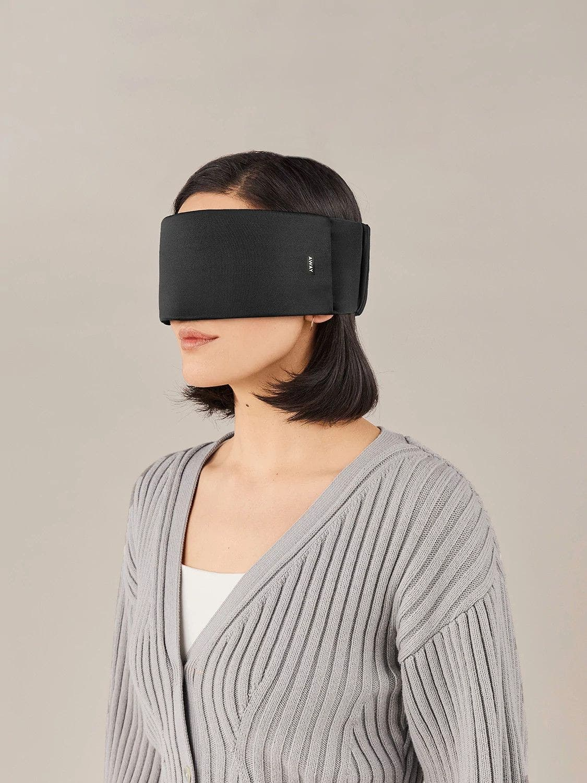 A woman wearing a black Away travel sleep mask across her eyes.