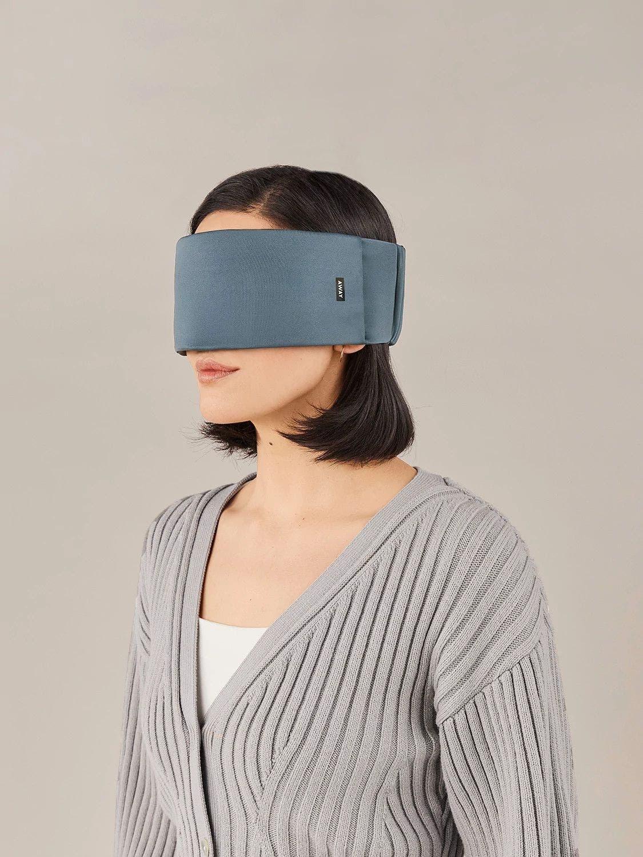 A woman wearing a blue Away travel sleep mask across her eyes.