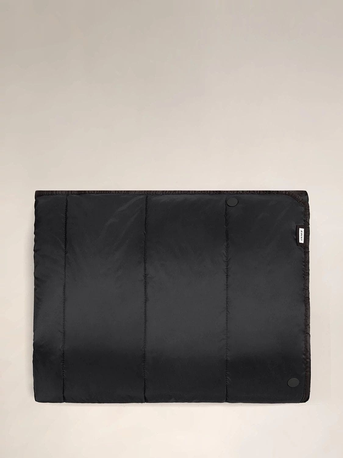 A black Away travel blanket laid flat front side up.