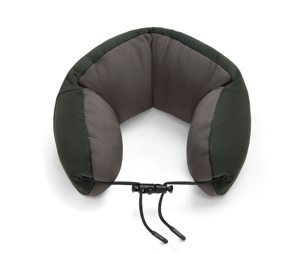 Aerial angled view of a green and grey travel neck pillow with a string loop on one side.