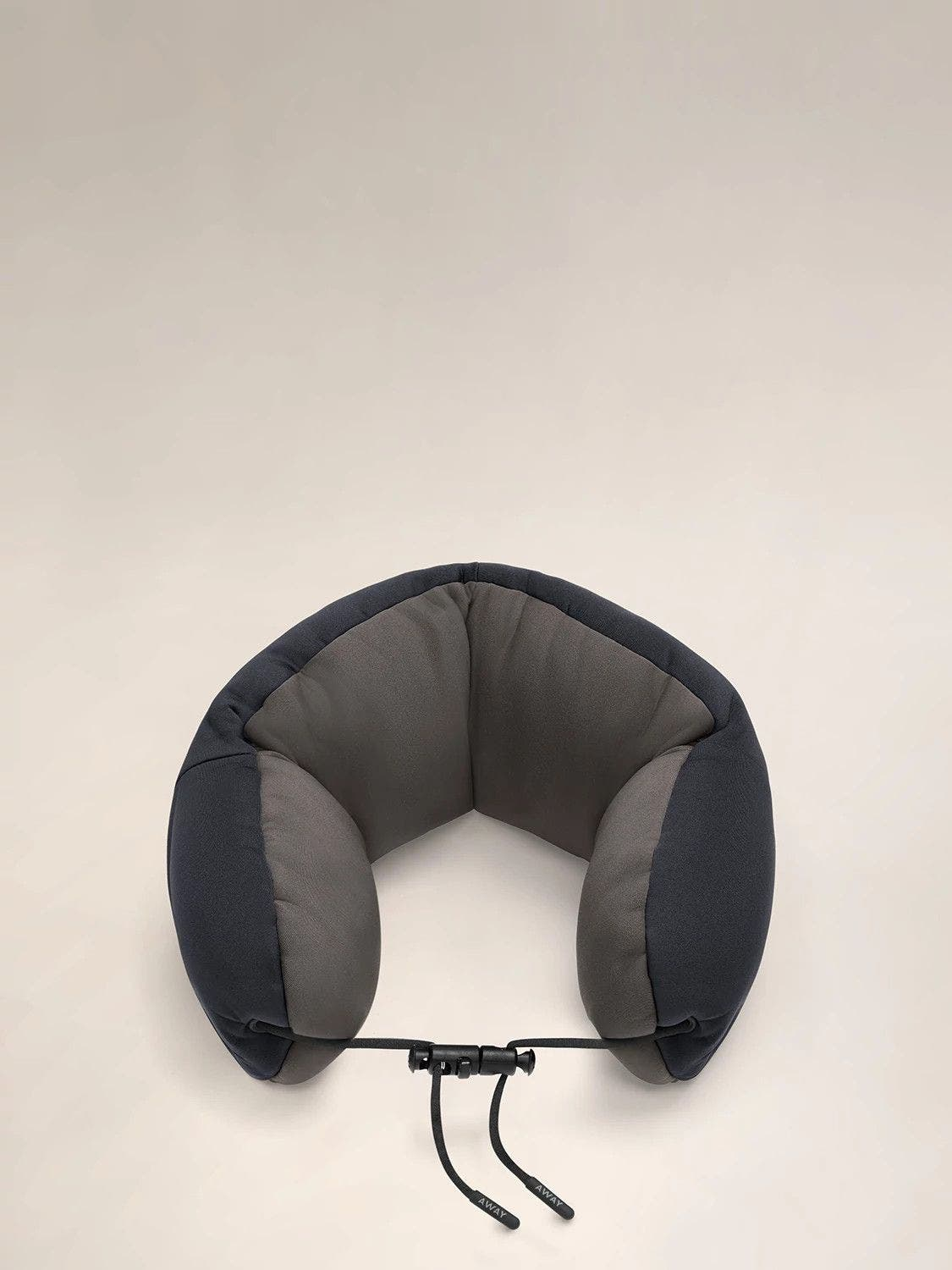 Aerial angled view of a navy and grey travel neck pillow with a string loop on one side.