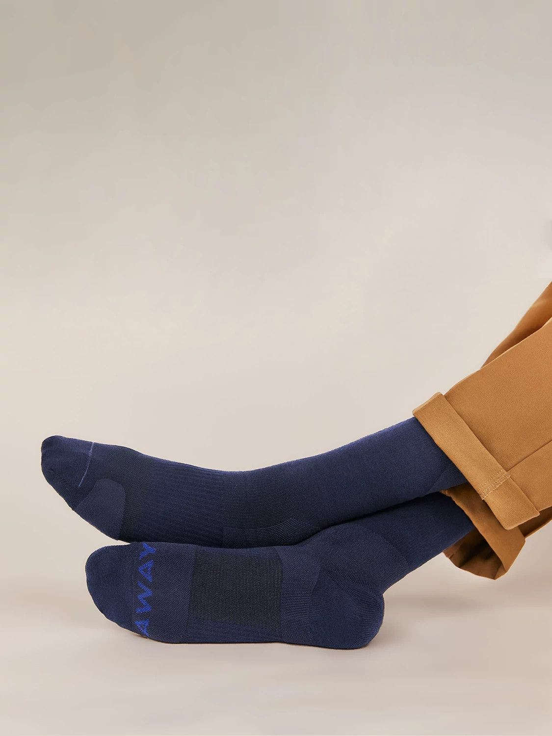 A person wearing navy blue Away compression socks for travel with legs stretched out.