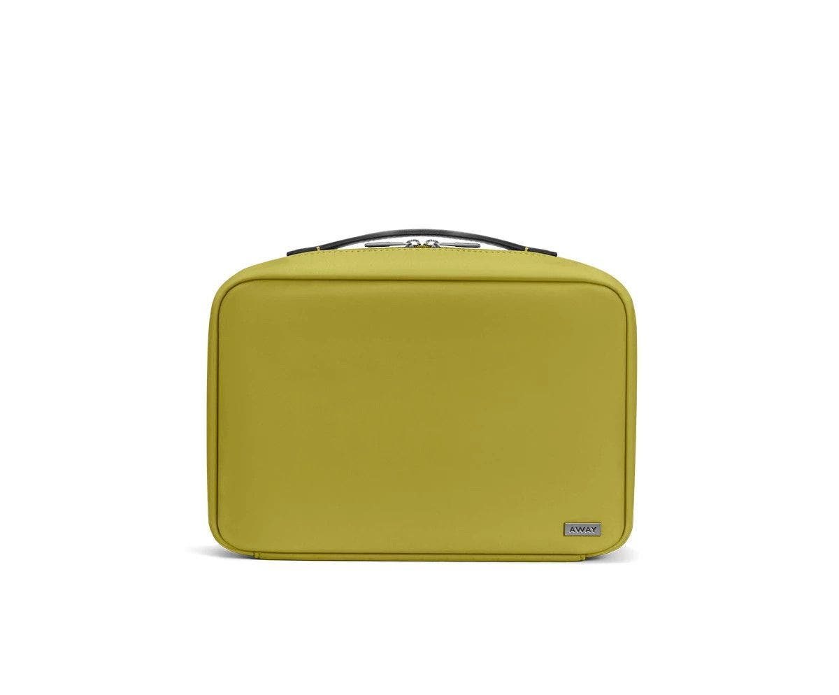 Front view of a pistachio green toiletry bag with handle on top.