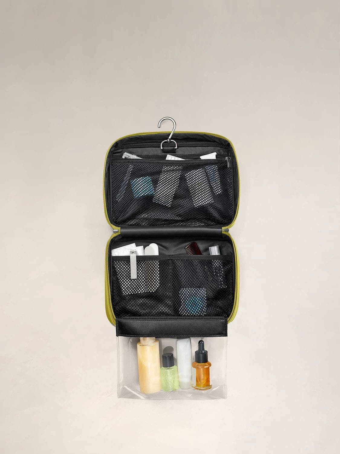 An internal view of a pistachio green toiletry bag packed with travel accessories within mesh pockets.