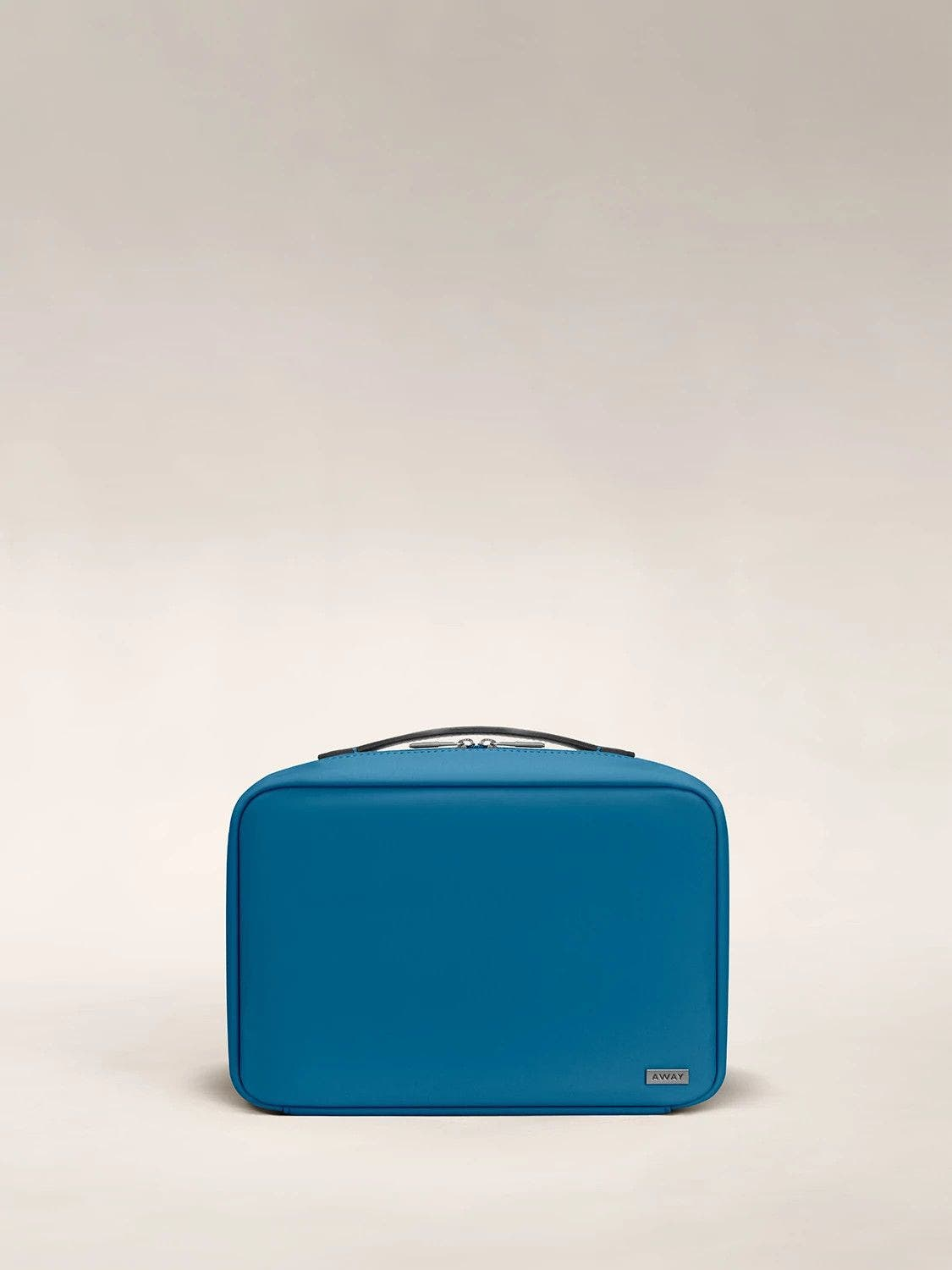 Front view of a deep teal toiletry bag with handle on top.