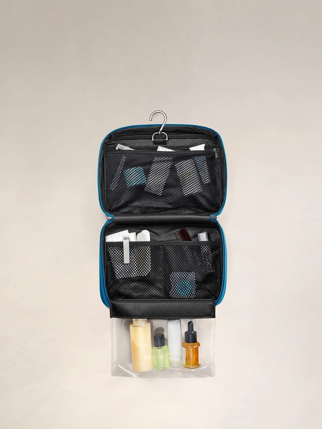 An internal view of a deep teal toiletry bag packed with travel accessories within mesh pockets.