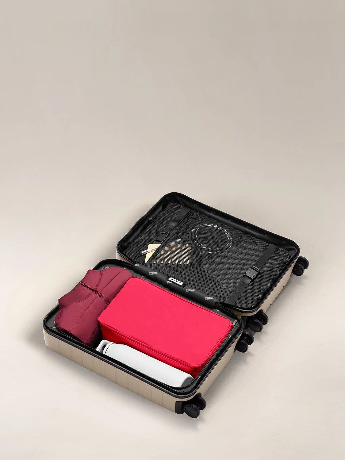 A large shoe cube in electric magenta packed in an open carry-on suitcase.